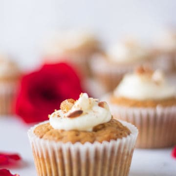 carrot cake cupcake with cream cheese frosting topped with almonds