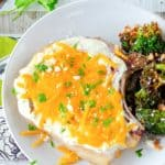 overhead view of cheesy sour cream baked pork chop and broccoli on a plate