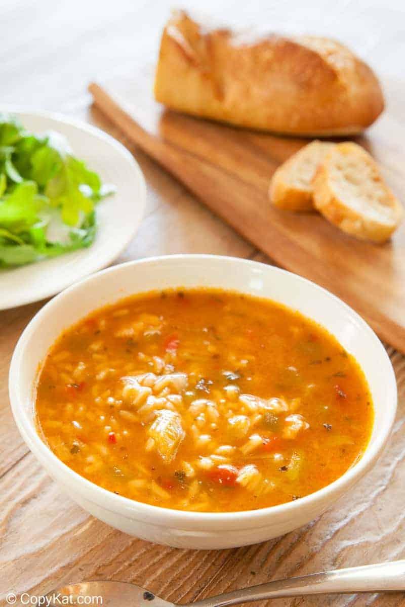 un tazón de sopa de pollo gumbo y pan sobre una tabla de cortar