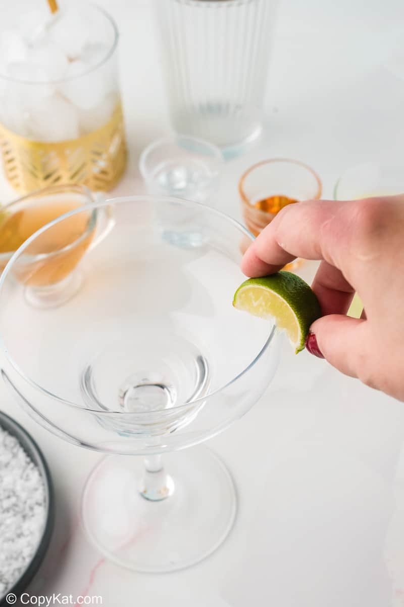 rubbing a lime wedge on the rim of a margarita glass