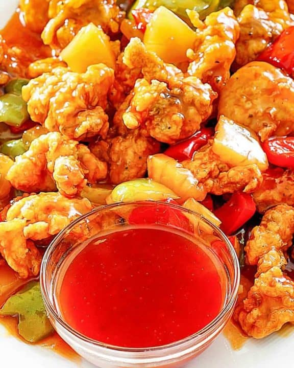 sweet and sour chicken and a bowl of homemade sweet and sour sauce