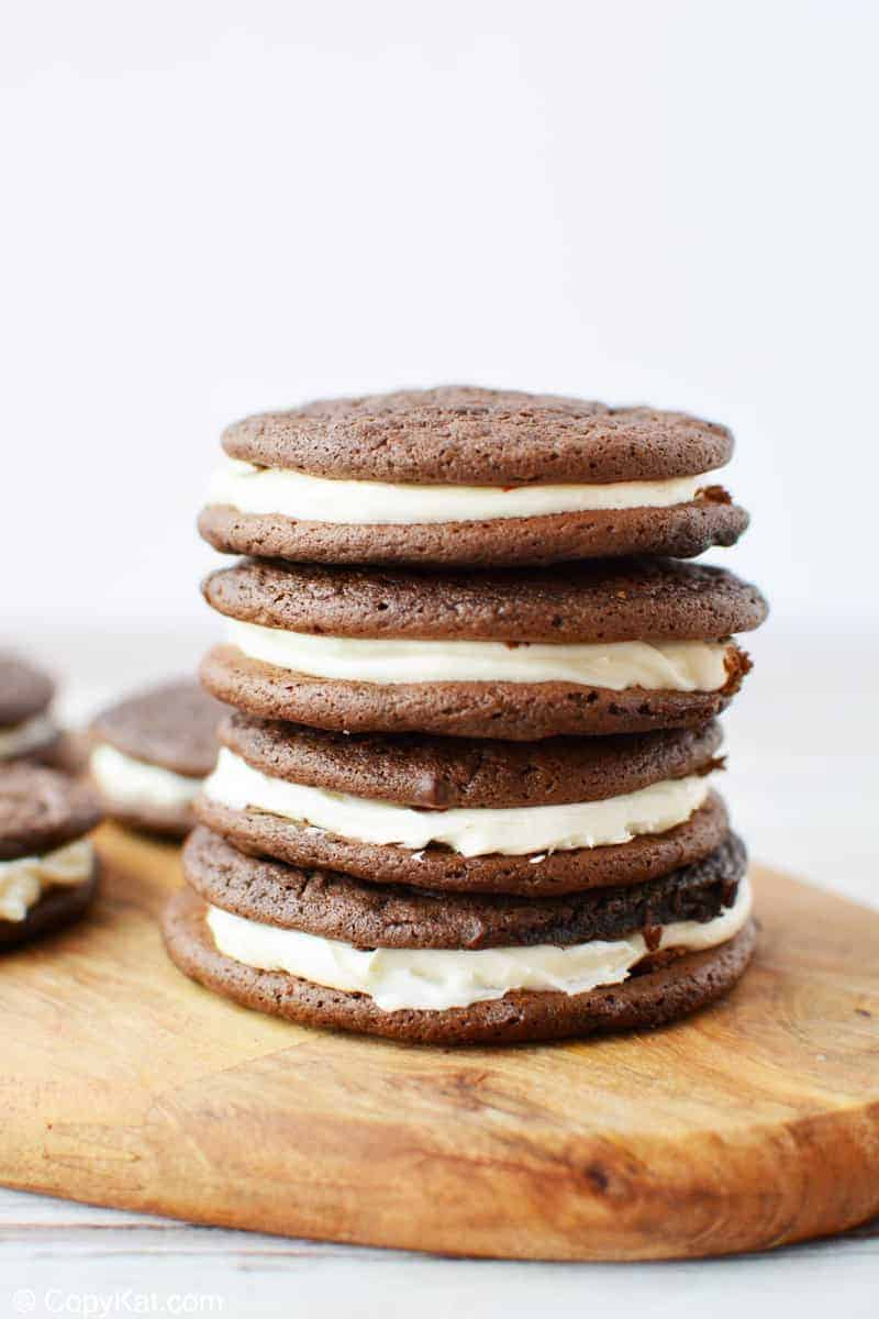 four chocolate sandwich cookies stacked on a wood board