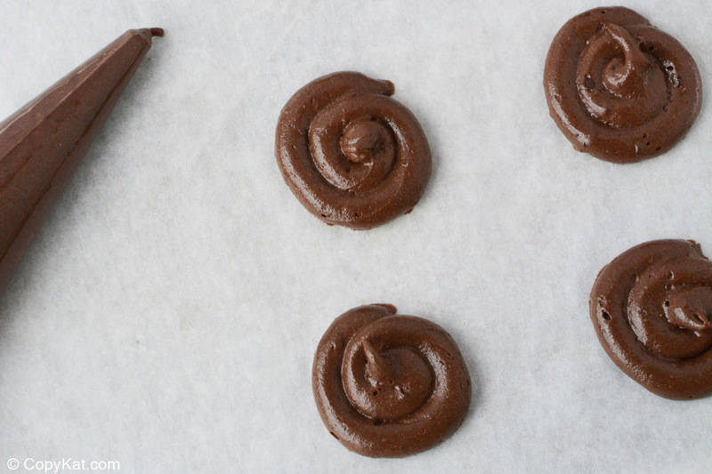 chocolate cookie batter piped into rounds on a baking sheet
