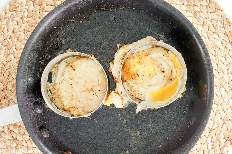 two fried eggs in rings in a skillet