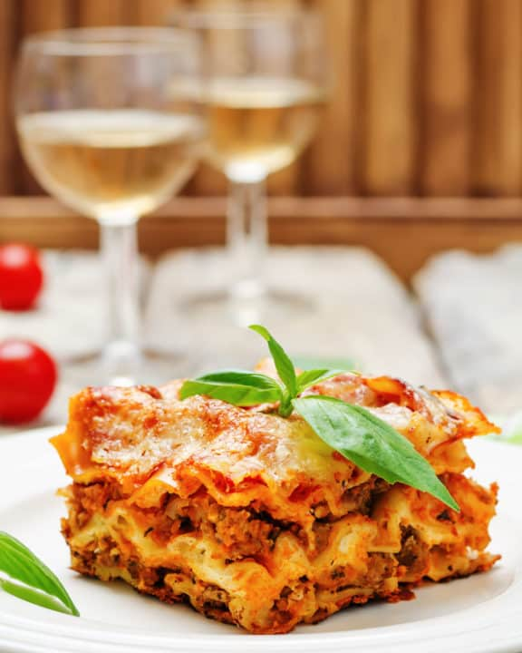 homemade lasagna on a plate and two glasses of white wine
