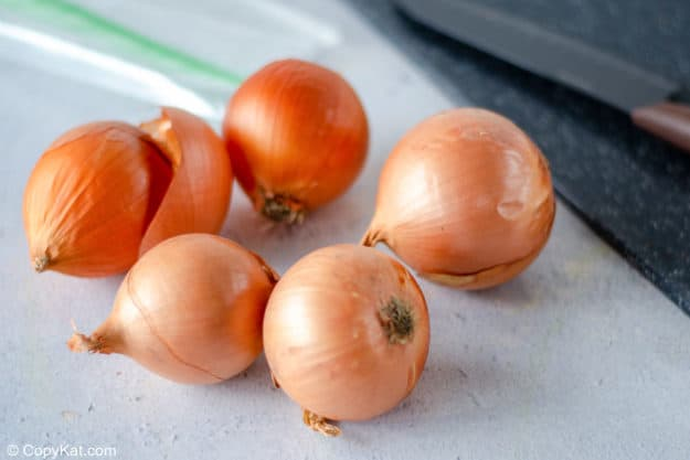 whole onions on a cutting board