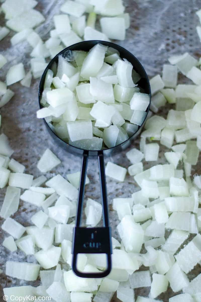 chopped onions in a measuring cup