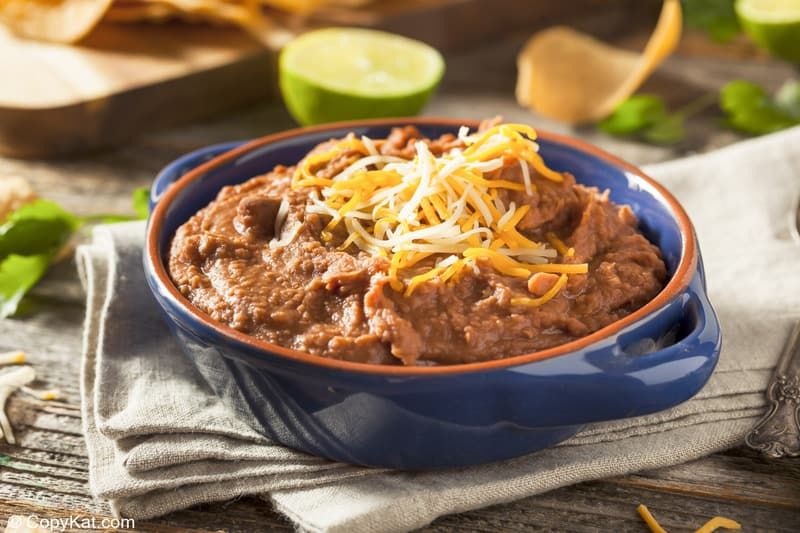 a bowl of homemade refried beans topped with shredded cheese in a bowl
