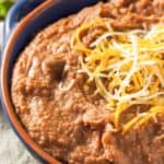 Instant Pot refried beans topped with shredded cheese in a bowl
