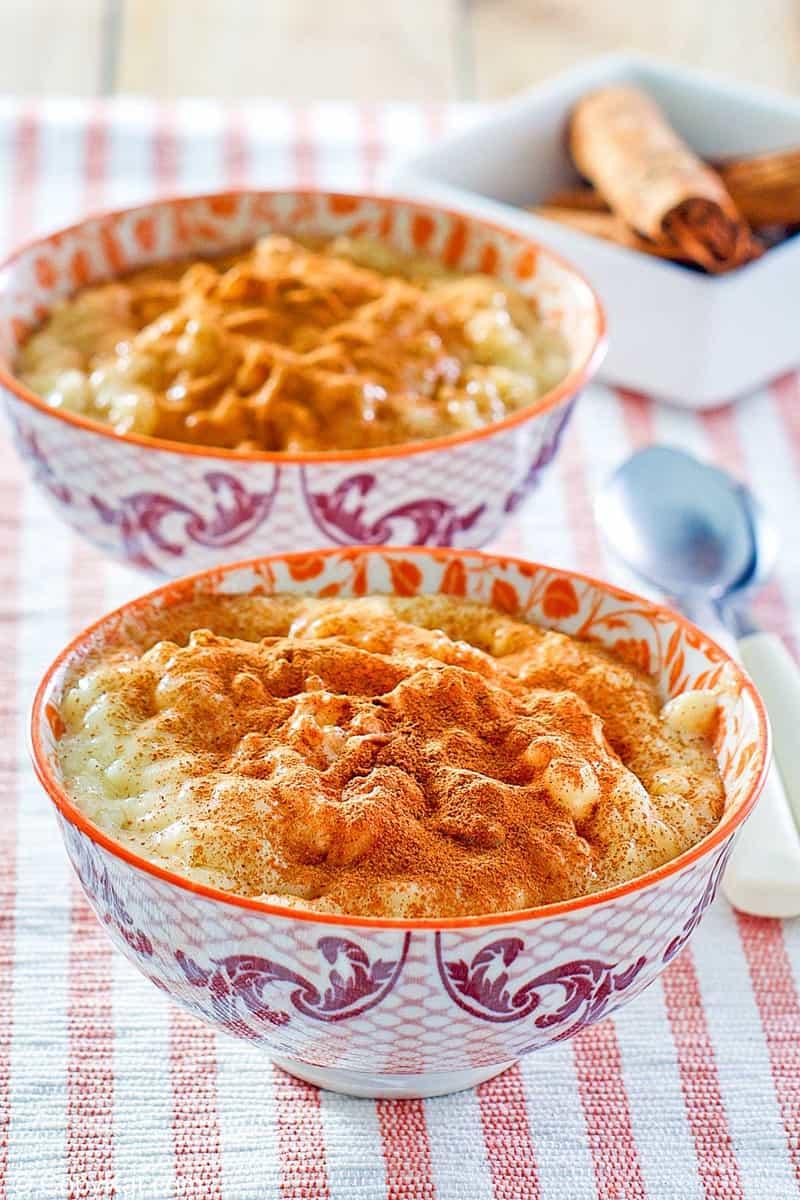 two bowls of homemade Kozy Shack rice pudding and cinnamon sticks