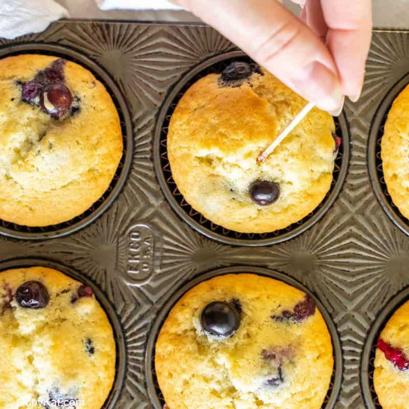 inserting a toothpick in a blueberry muffin to test for doneness