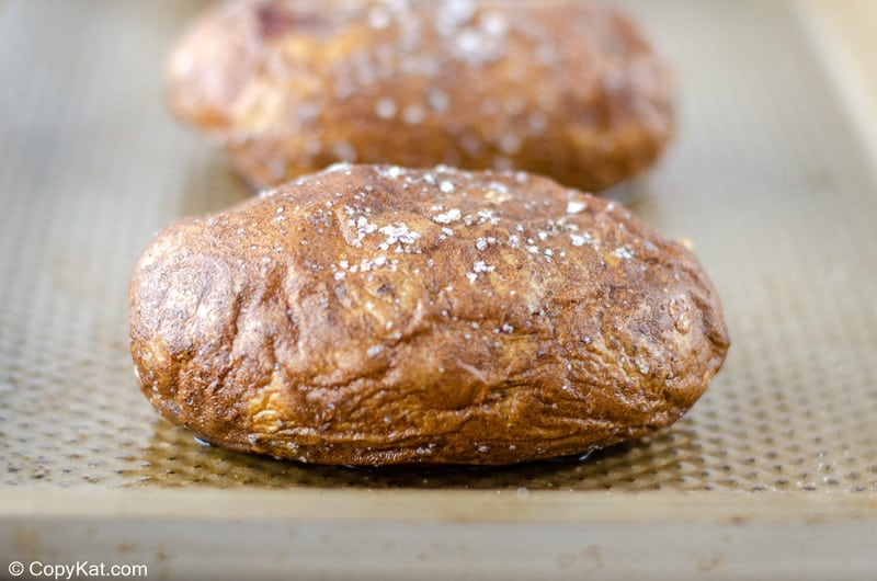 baked russet potato with salt on a baking sheet