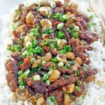 Mongolian beef with mushrooms over rice on a platter