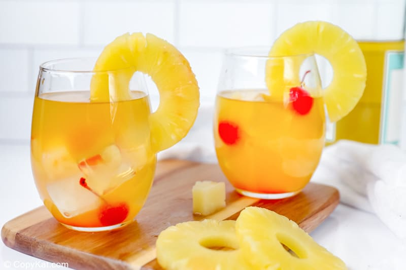 two glasses of pineapple white wine sangria garnished with pineapple ring