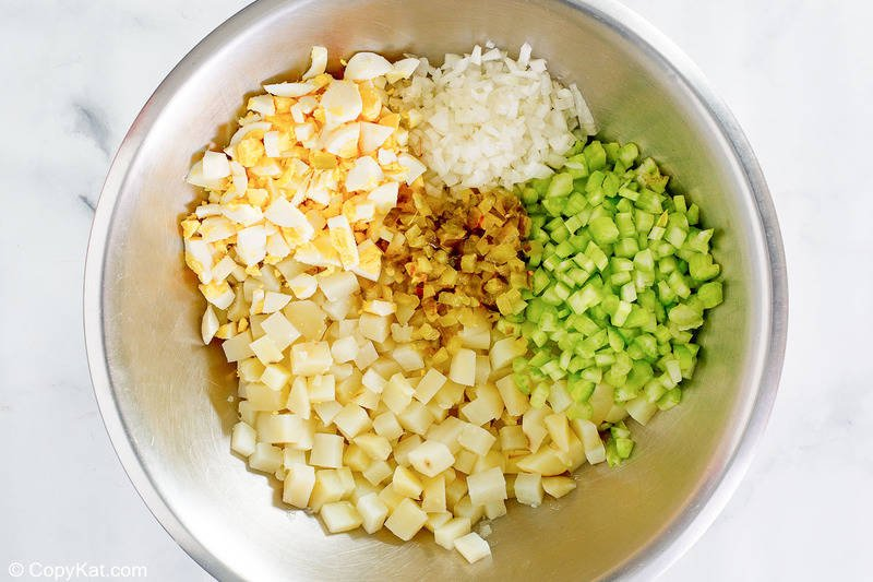 chopped potatoes, eggs, onions, celery, and pickles in a bowl