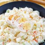 homemade potato salad topped with sliced egg in a bowl