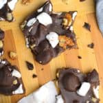 overhead view of rocky road candy with walnuts on a wood board