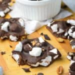 rocky road candy with walnuts in a bowl and on a wood board