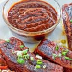 a bowl of homemade BBQ sauce and ribs on a plate