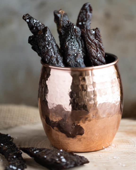 pieces of homemade teriyaki beef jerky in a cup
