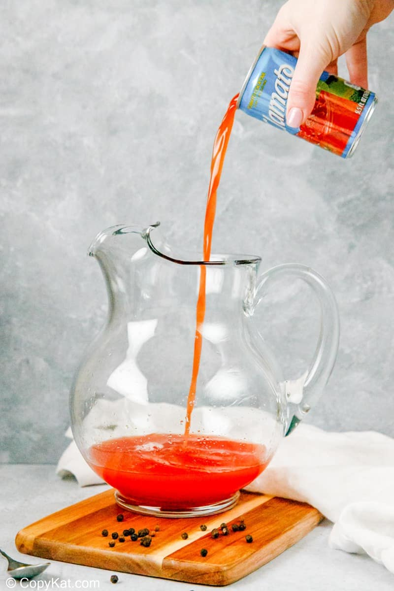 pouring Clamato juice into a pitcher