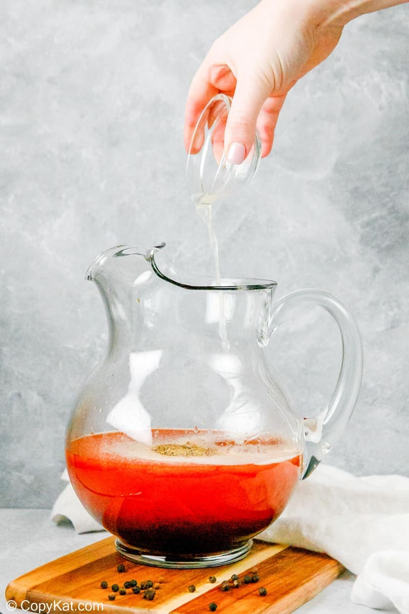 pouring lemon juice into a pitcher of homemade bloody mary mix