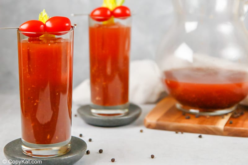 two bloody mary cocktails and bloody mary mix in a pitcher