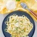 Vista aérea de fideos fettuccine con salsa alfredo cremosa y queso parmesano