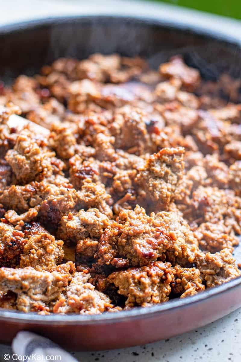 seasoned ground beef cooking in a skillet