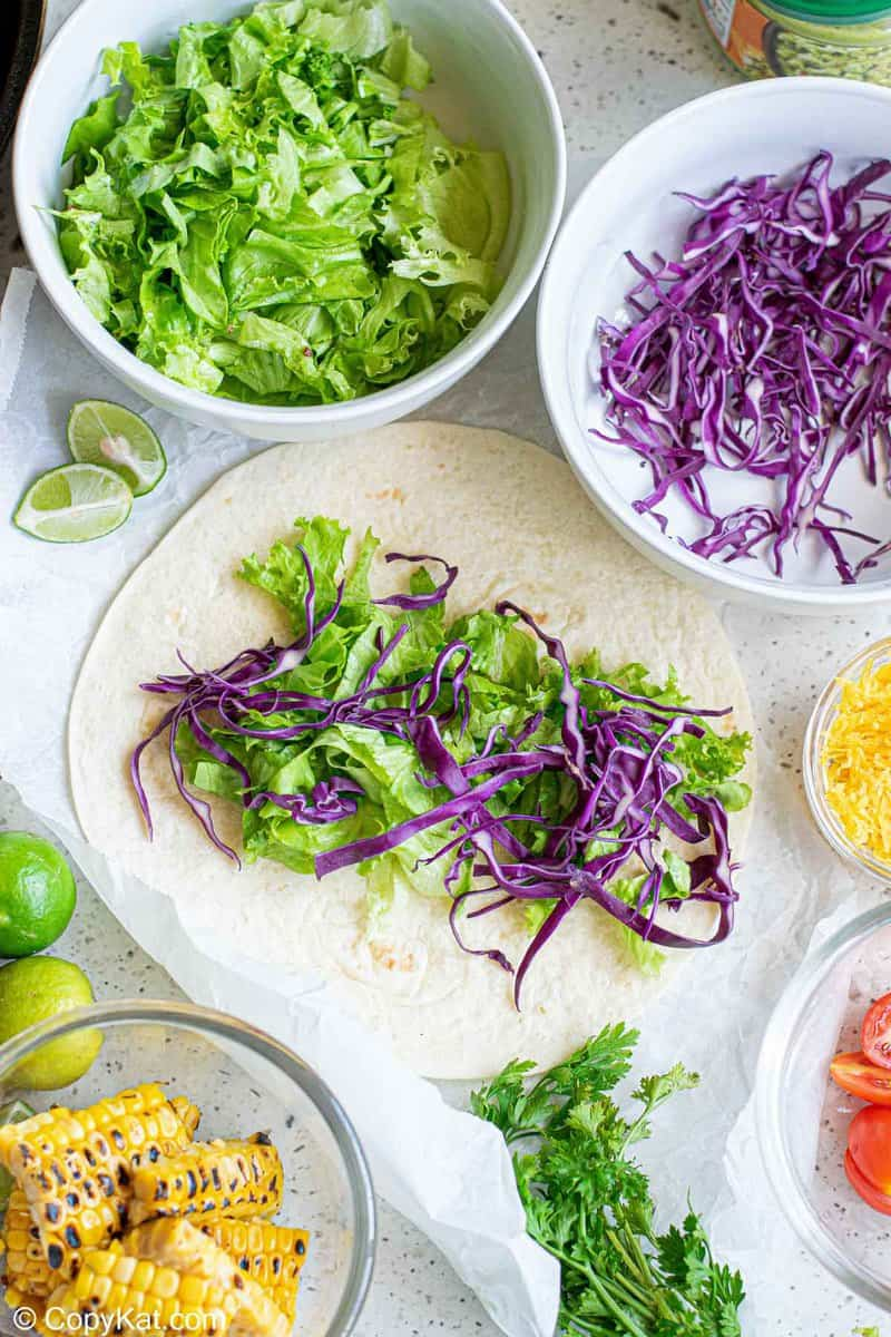 lettuce and red cabbage on a flour tortilla
