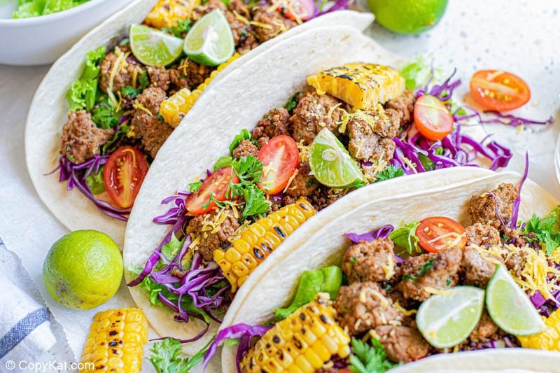 three ground beef tacos with soft flour tortillas