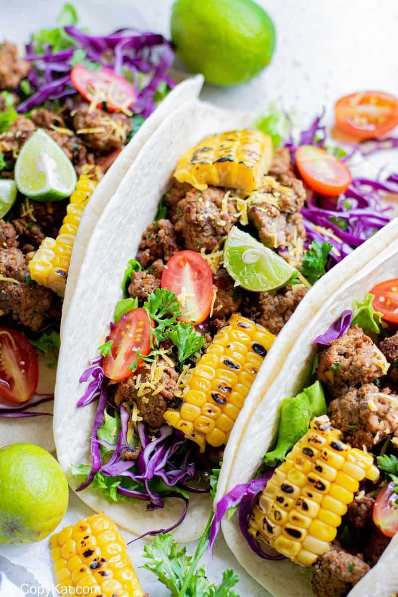 three ground beef tacos with toppings
