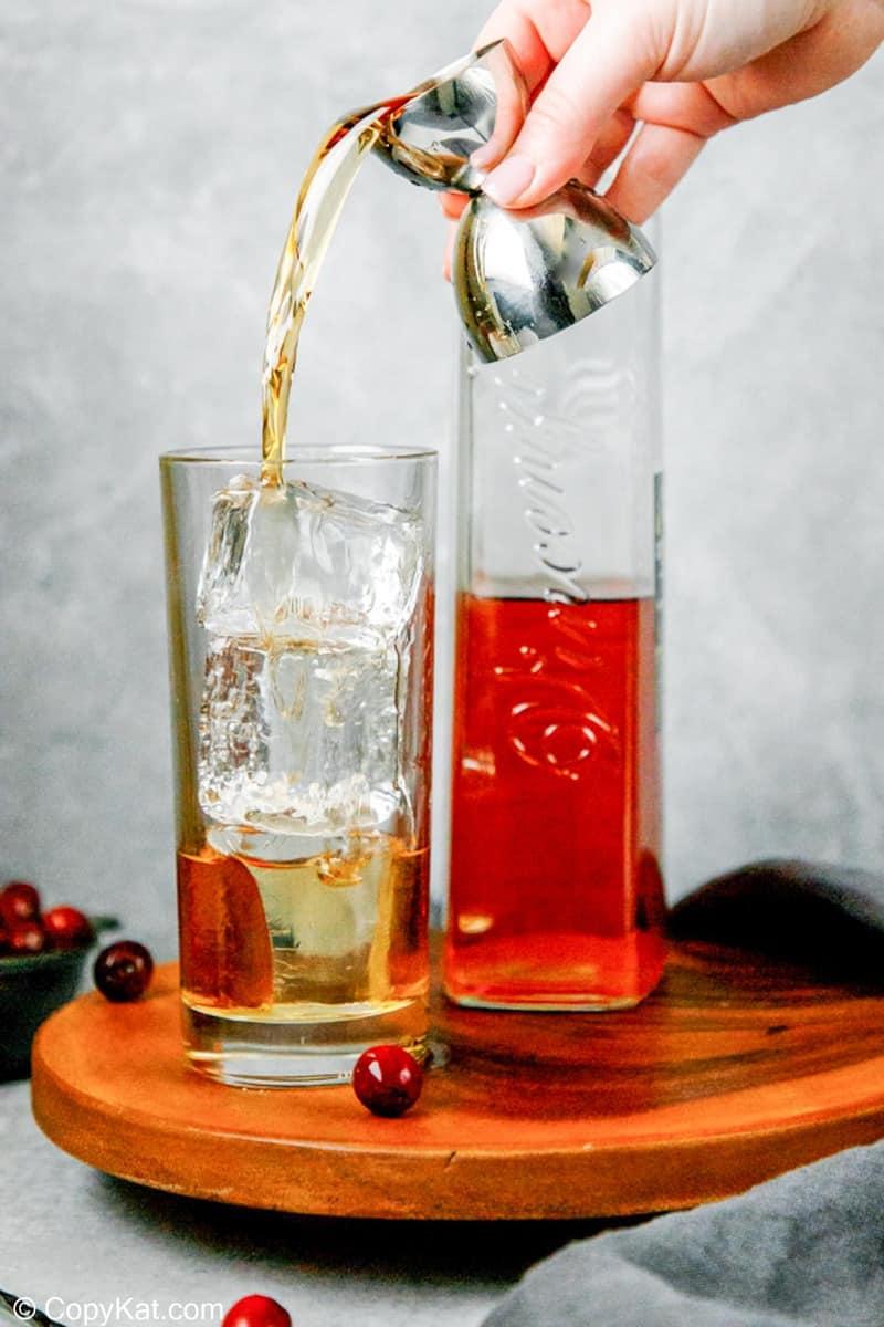vertiendo amaretto en un vaso con hielo