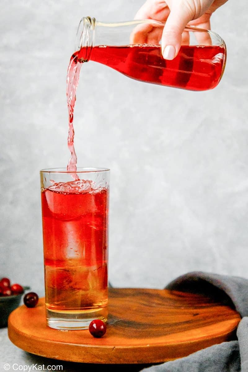 vertiendo jugo de arándano en un vaso con hielo