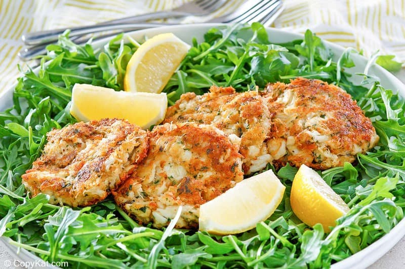 Maryland crab cakes and lemon wedges on top of arugula