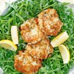 overhead view of four Maryland crab cakes and lemon wedges on top of arugula