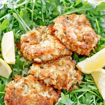 four Maryland crab cakes, lemon wedges, and arugula on a platter