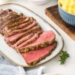 NY tiras de asado en rodajas en un plato junto a tazones de brócoli y patatas