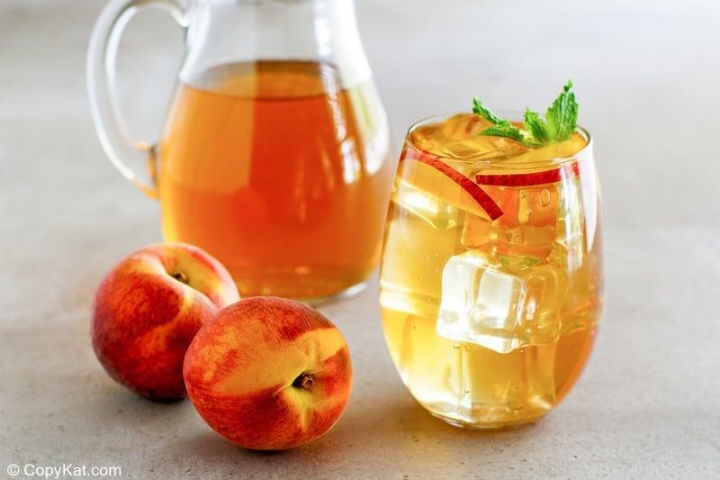 a glass of peach iced tea and two fresh peaches
