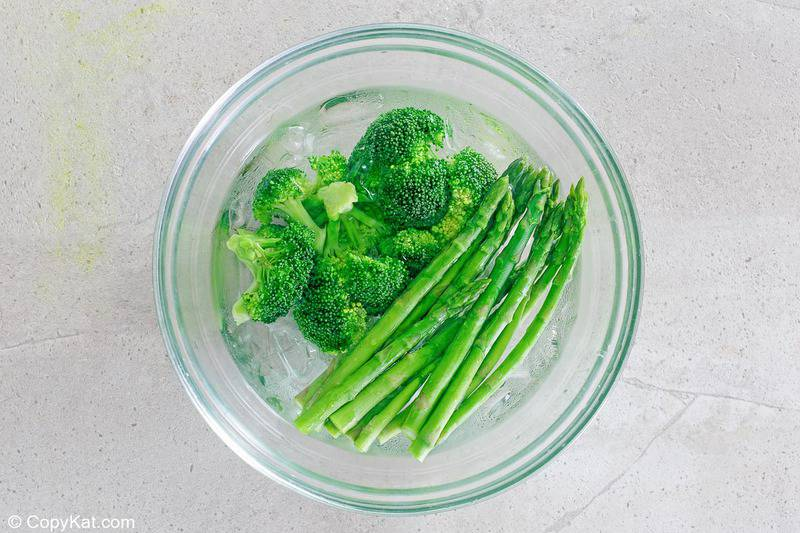 blanched asparagus and broccoli in an ice bath