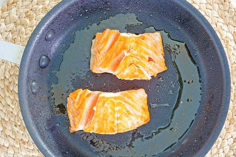 frying two pieces of salmon in a skillet