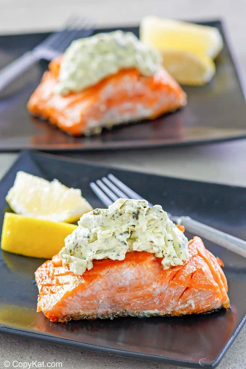 two servings of pan fried salmon with pesto cream cheese sauce