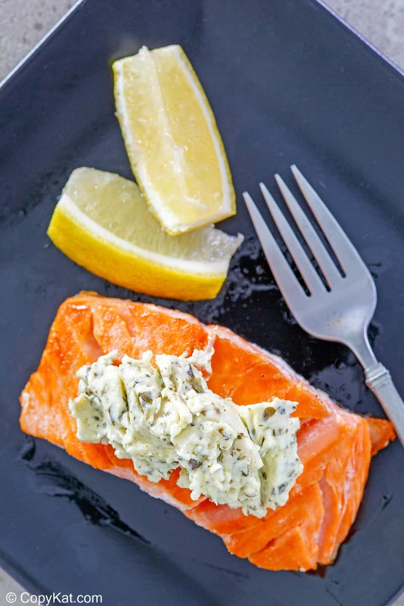 overhead view of salmon with pesto cream cheese sauce and two lemon wedges on a plate