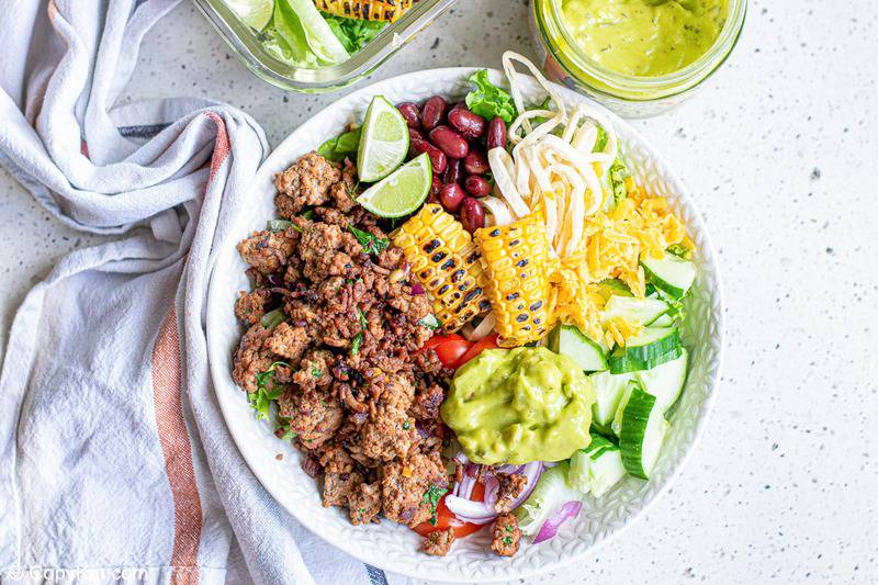ground beef taco bowl with cheese, guacamole, beans, and vegetables