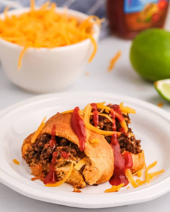 piece of a taco ring on a plate and a bowl of shredded cheese