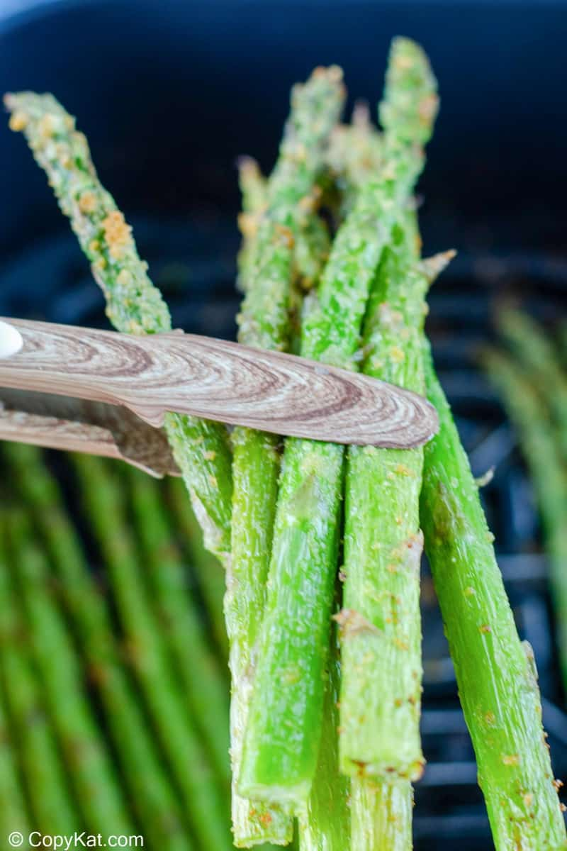 tongs holding air fried asparagus spears over a air fryer basket