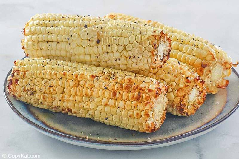 4 air fried corn on the cob pieces on a plate