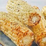 4 ears of air fried corn on the cob stacked on a plate