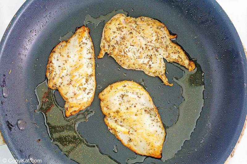 marinated chicken cooking in a skillet