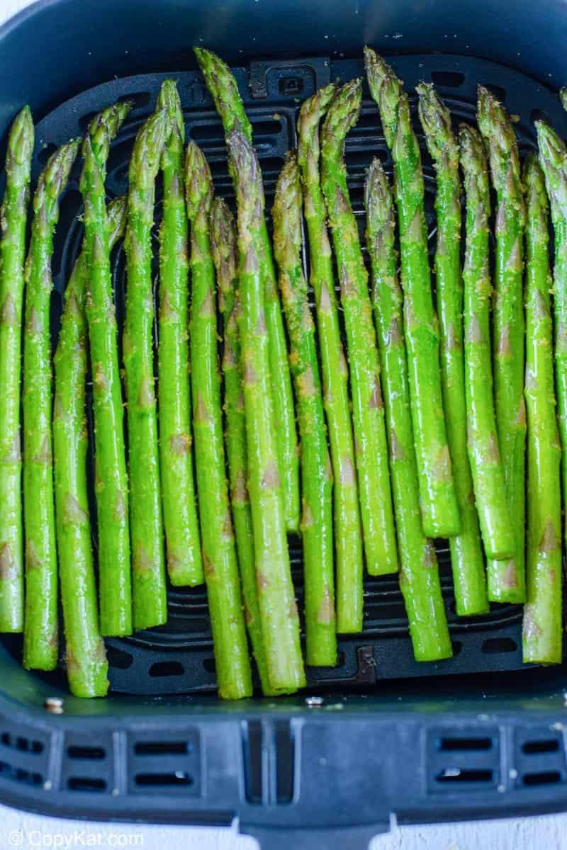 fresh asparagus in an air fryer basket